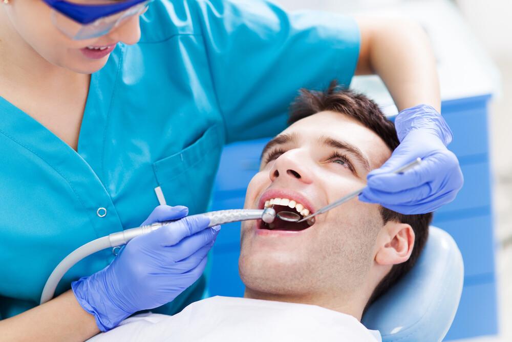 female dentist examining male patient