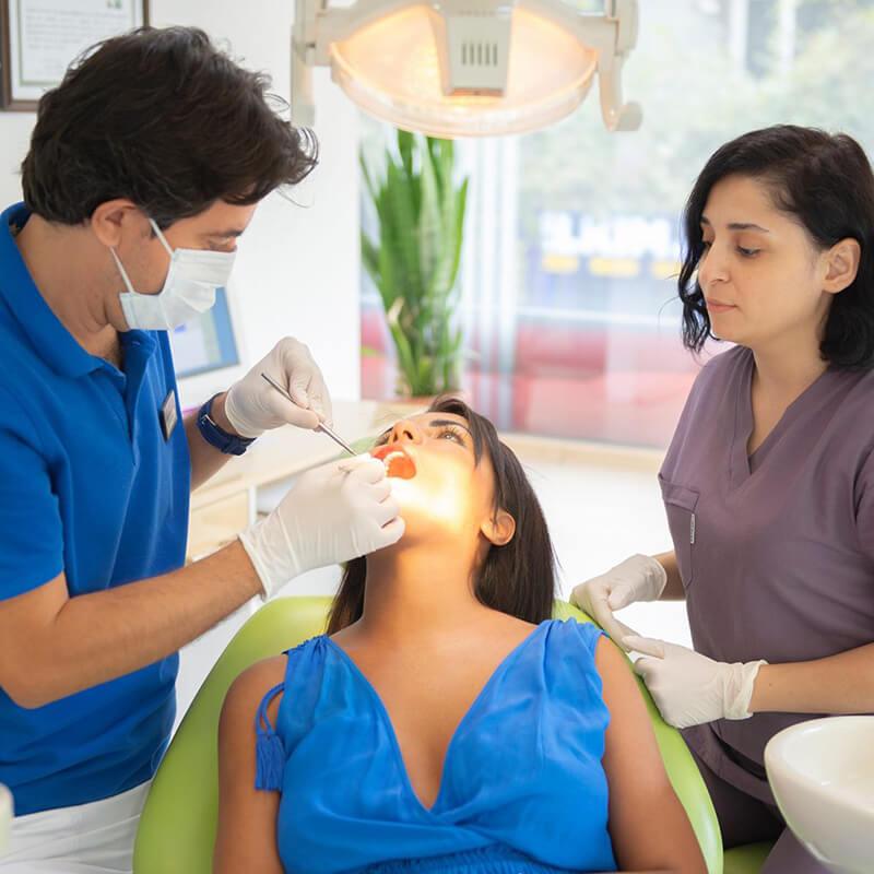 dentiste soigne une patiente avec assistant